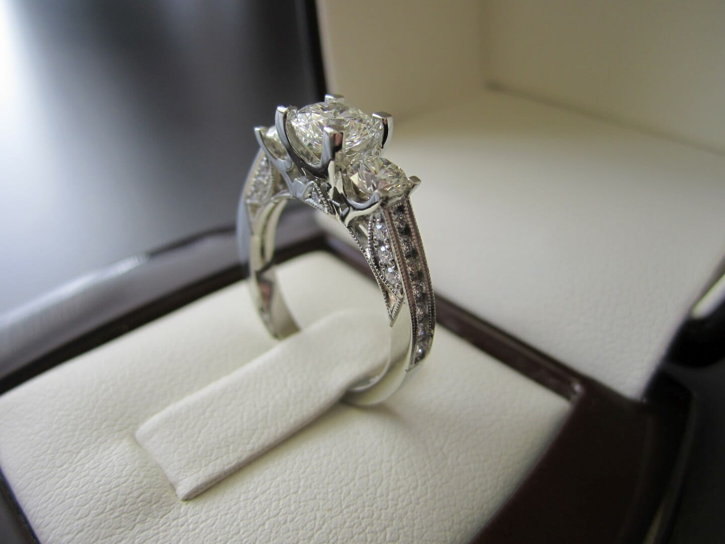 Picture of Custom 3 Stone Engagement Ring with Accent Diamonds and Milgrain in 19K White Gold